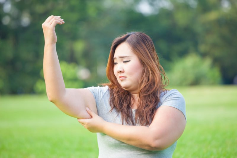 woman frustrated with her stubborn arm fat