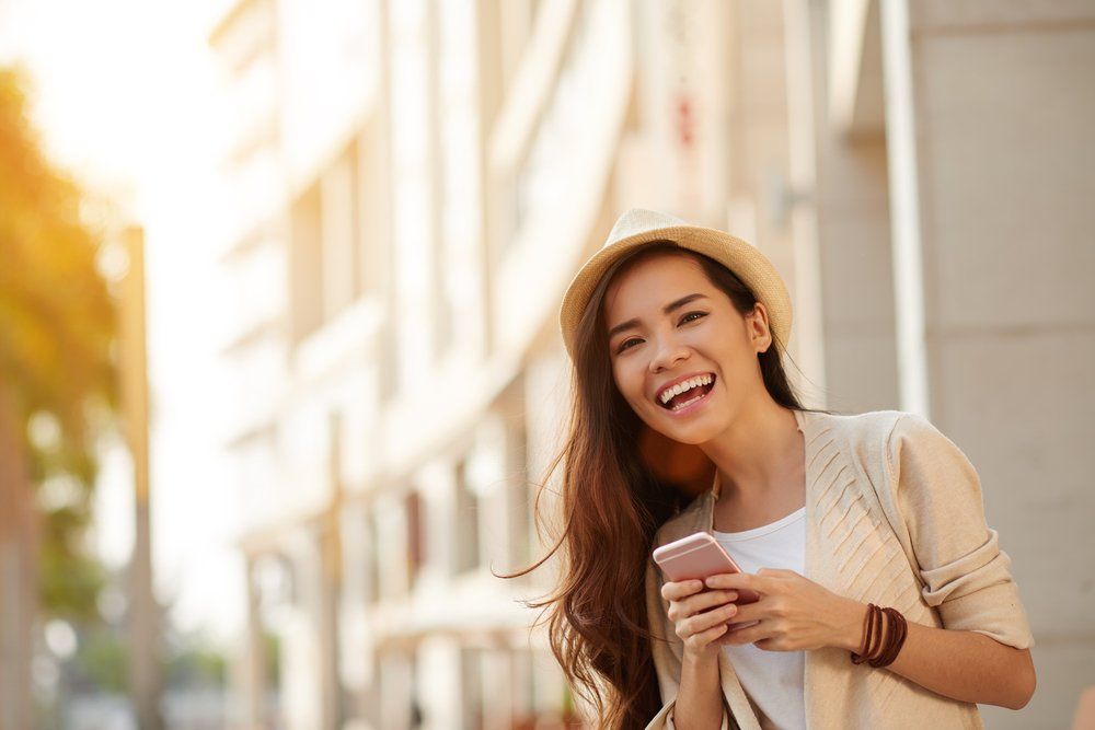 Woman smiling on her phone and in a good mood — natural mood enhancers