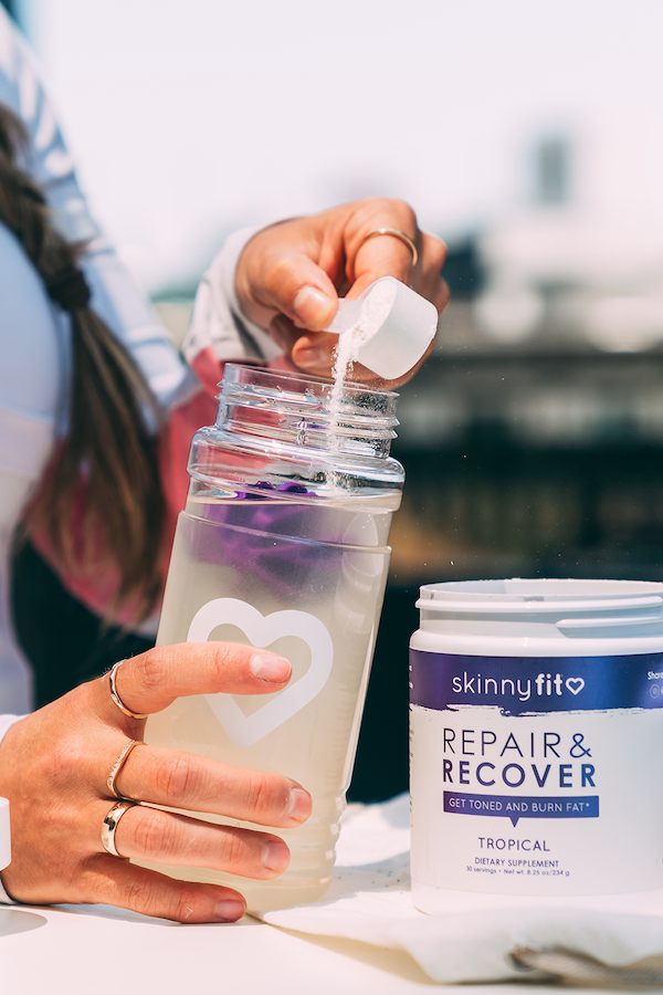 SkinnyFit electrolyte powder Repair & Recover being poured into a water bottle