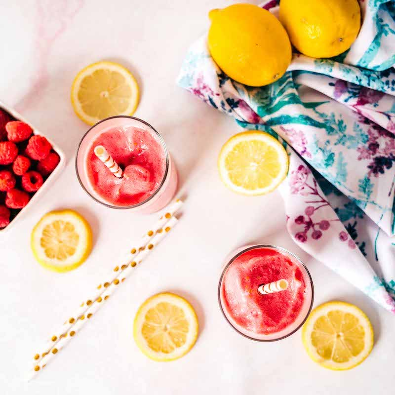 Frozen lemonade slushies with Super Youth Tropical Punch collagen surrounded by lemon slices and fresh raspberries.