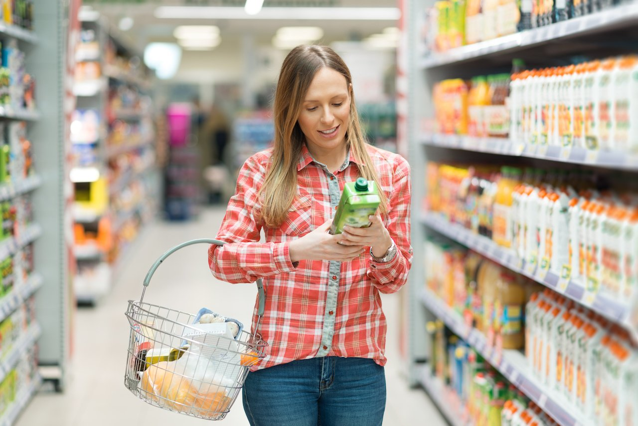 A woman in a food store reading a nutrition label on a carton of juice