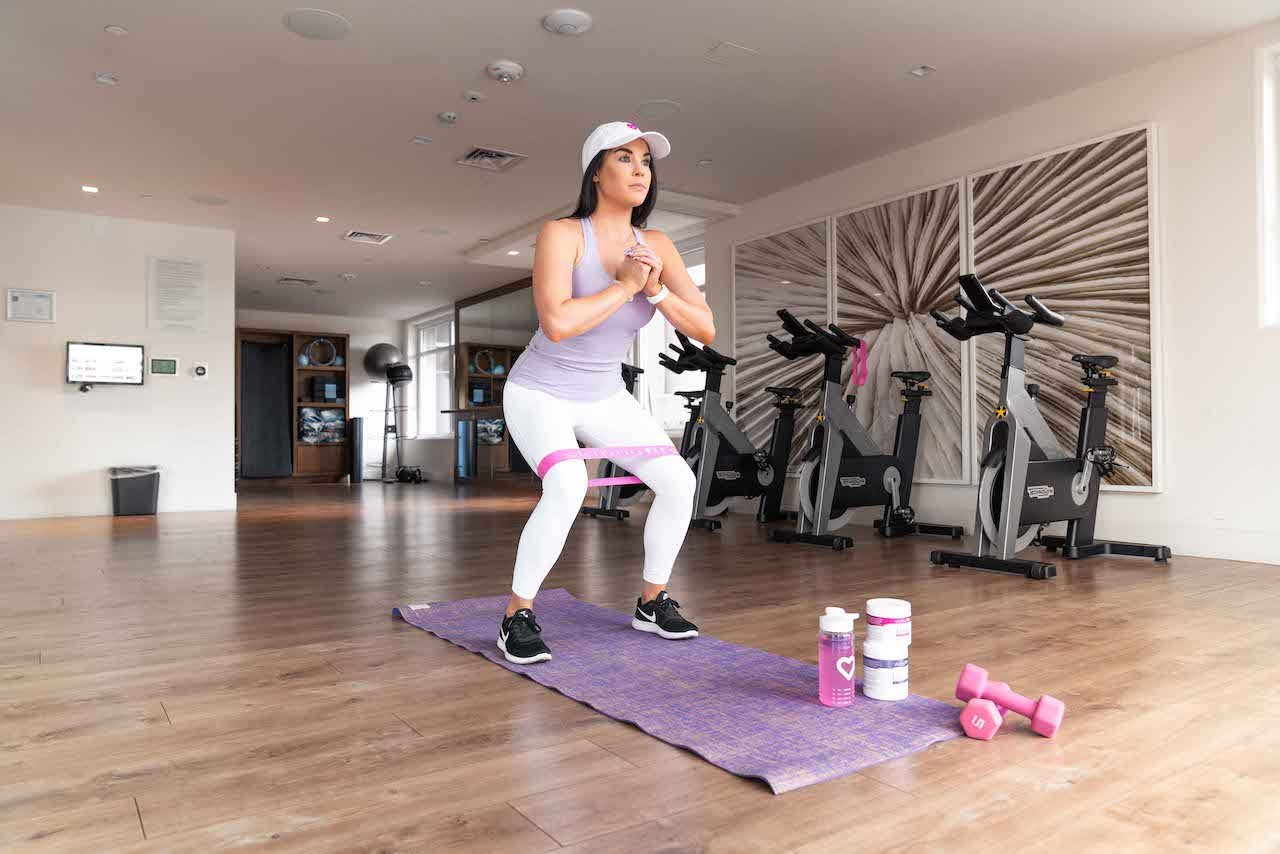 Woman doing HIIT for beginners workout with SkinnyFit Repair & Recover and Jump Start workout supplements.