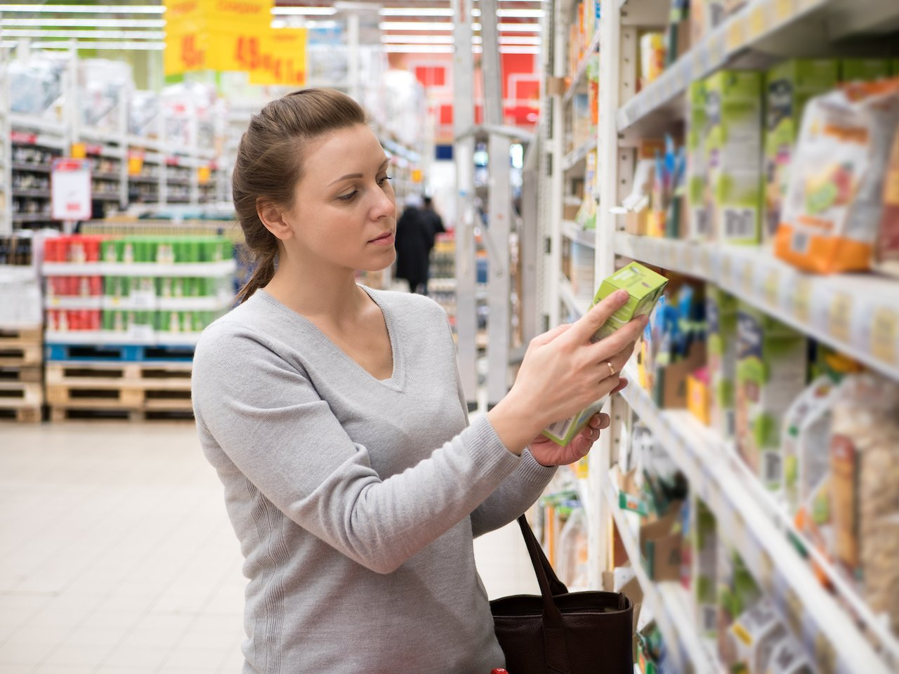 A woman in the food store carefully reading the nutrition label on snack food.