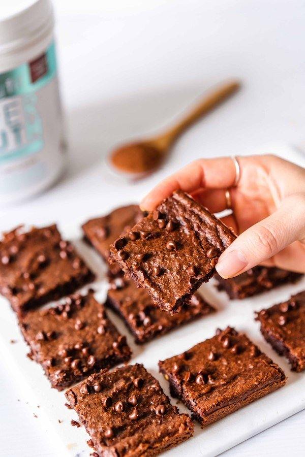 A hand holding on of the SkinnyFit Super Youth collagen healthy brownies, about to take a bite.
