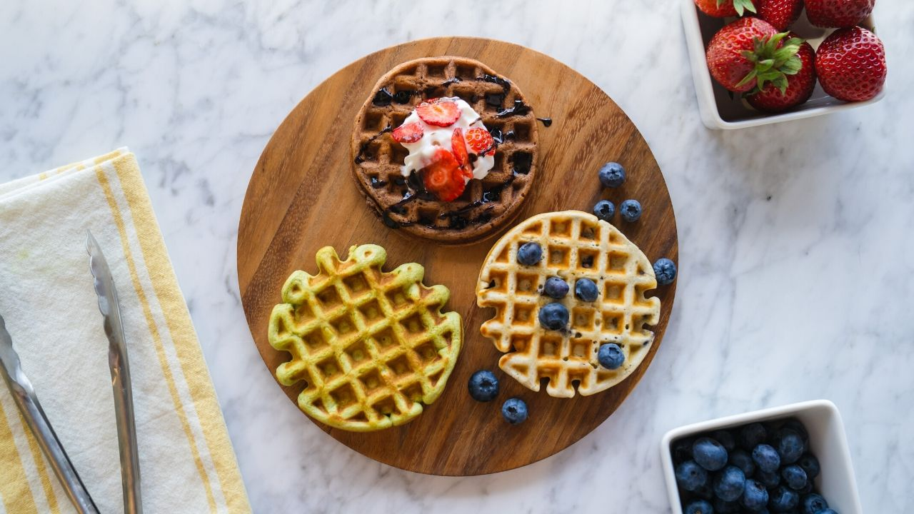 Homemade waffles in different flavors with blueberries and strawberries
