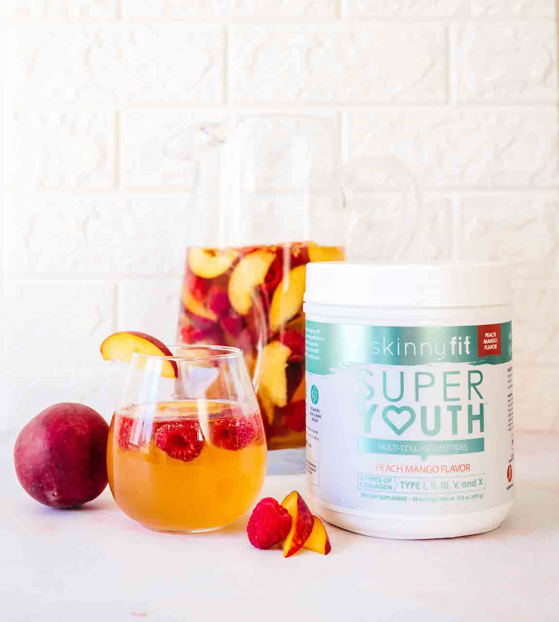 Peach Rose Sangria in a wine glass beside fresh fruit and SkinnyFit Super Youth Peach Mango Collagen Peptides
