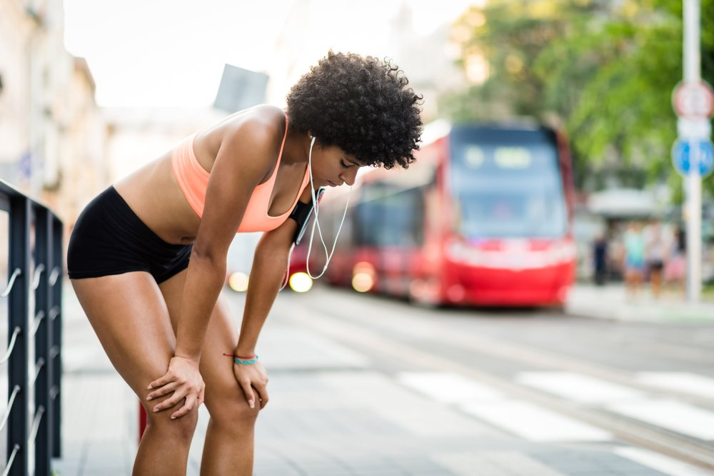 overtraining - woman trying to catch her breath while running