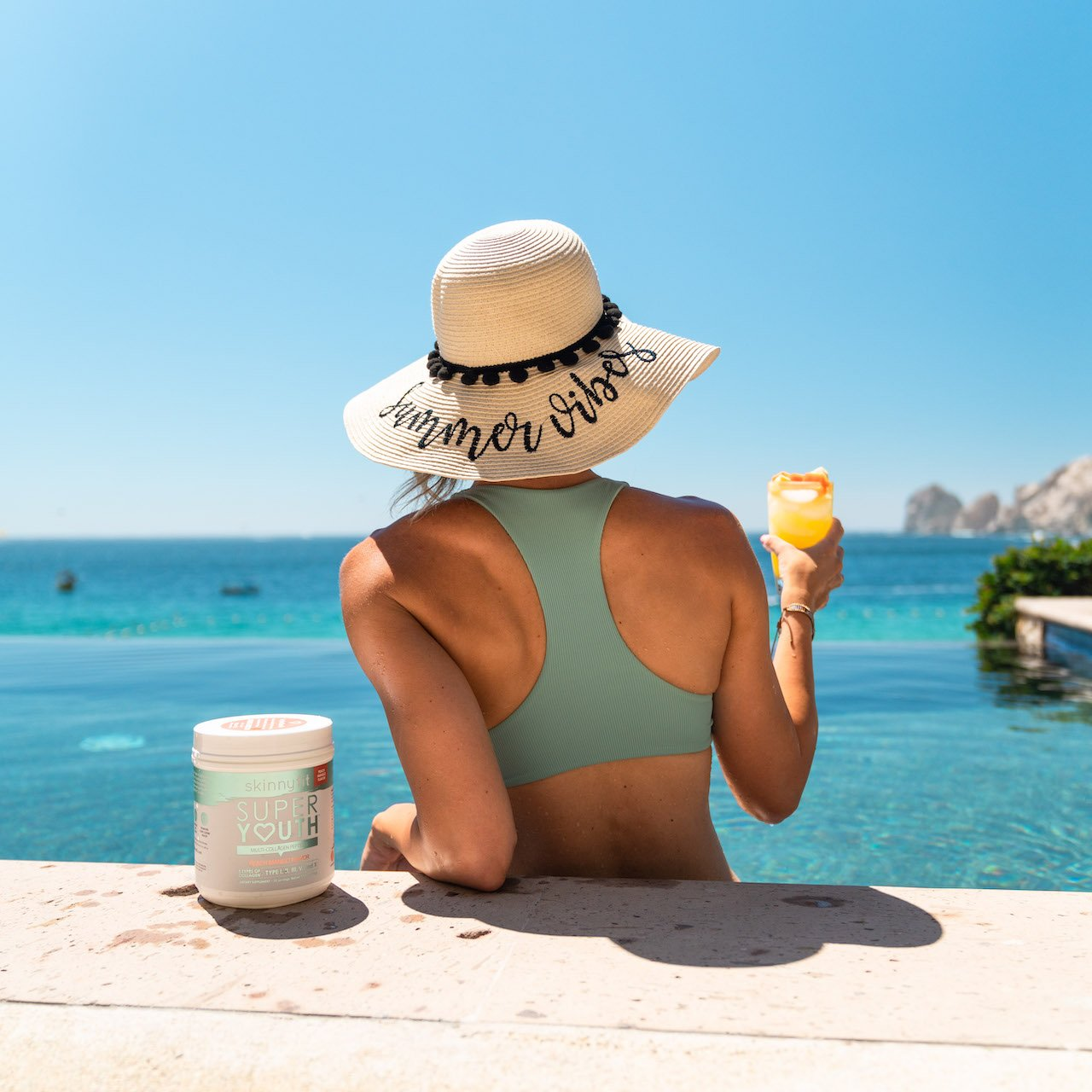 Woman in an infinity pool drinking SkinnyFit Super Youth collagen peptides to help cracking joints