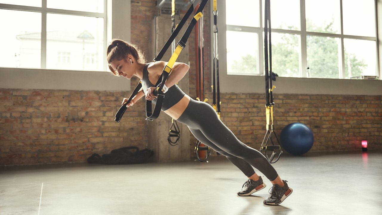 Althetic woman performing chest press suspension training.