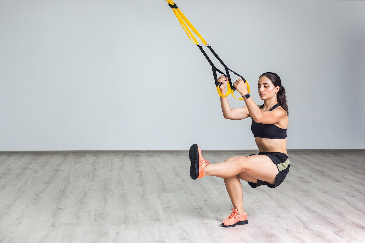 Woman performing an extended leg lunge with TRX suspension training equipment
