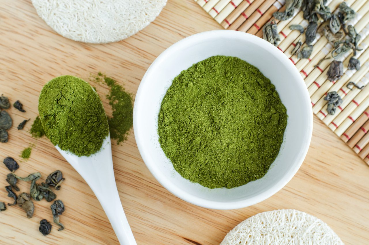 Spirulina powder in a bowl and spoon.
