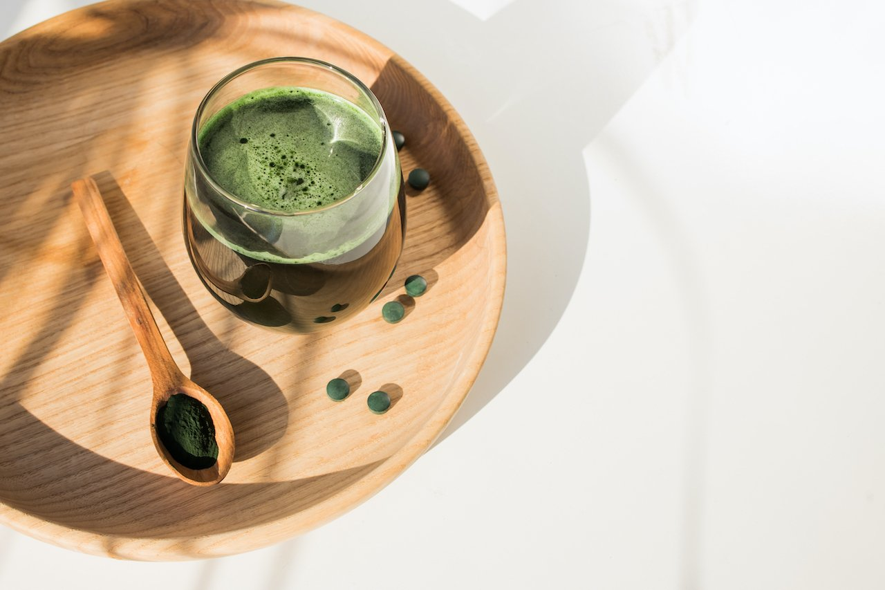 Glass of chlorella on a wooden serving plate.