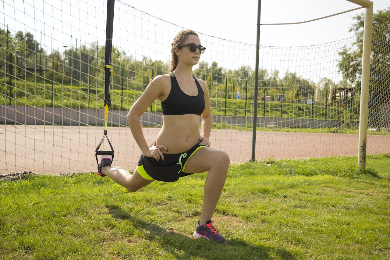 Woman performing a balancing lunge with her foot in her TRX suspension training handle for added difficulty.