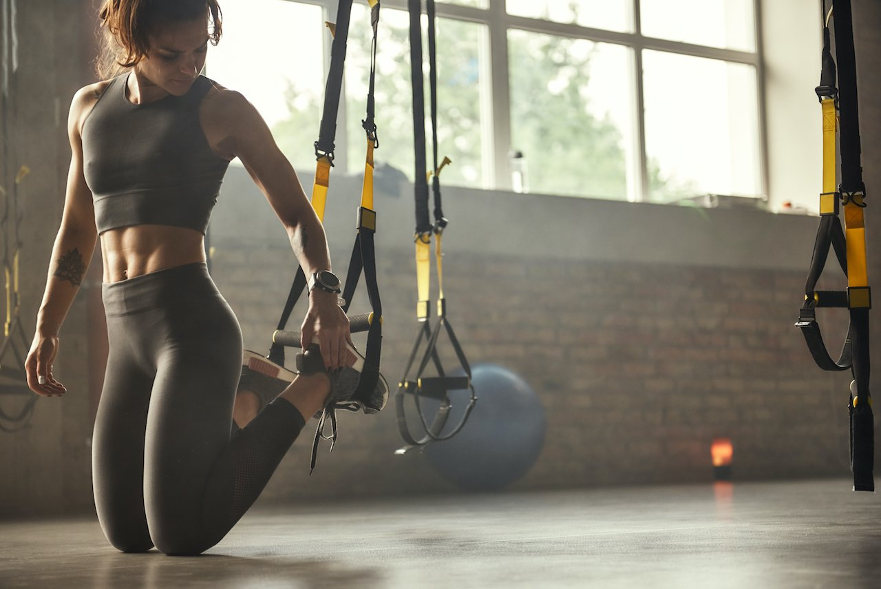 Woman with great core strength setting up for TRX suspension training