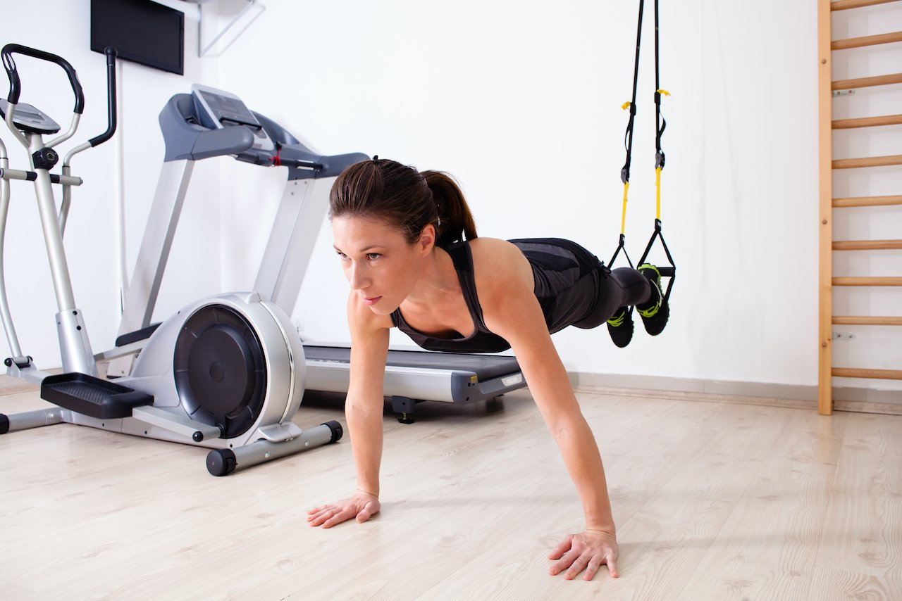 Woman performing a suspended pushup with TRX suspension training gear