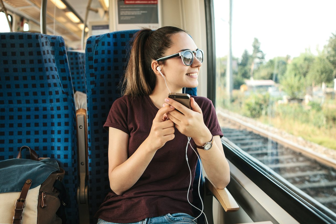 A girl listens to a podcast while commuting on a train.