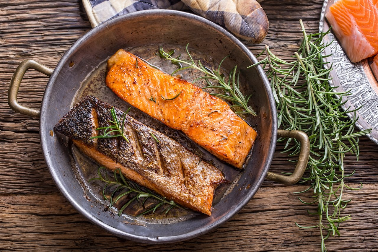 A cast iron skillet with two seasoned salmon BBQ filets. Eating protein can help you push through weight loss plateau.