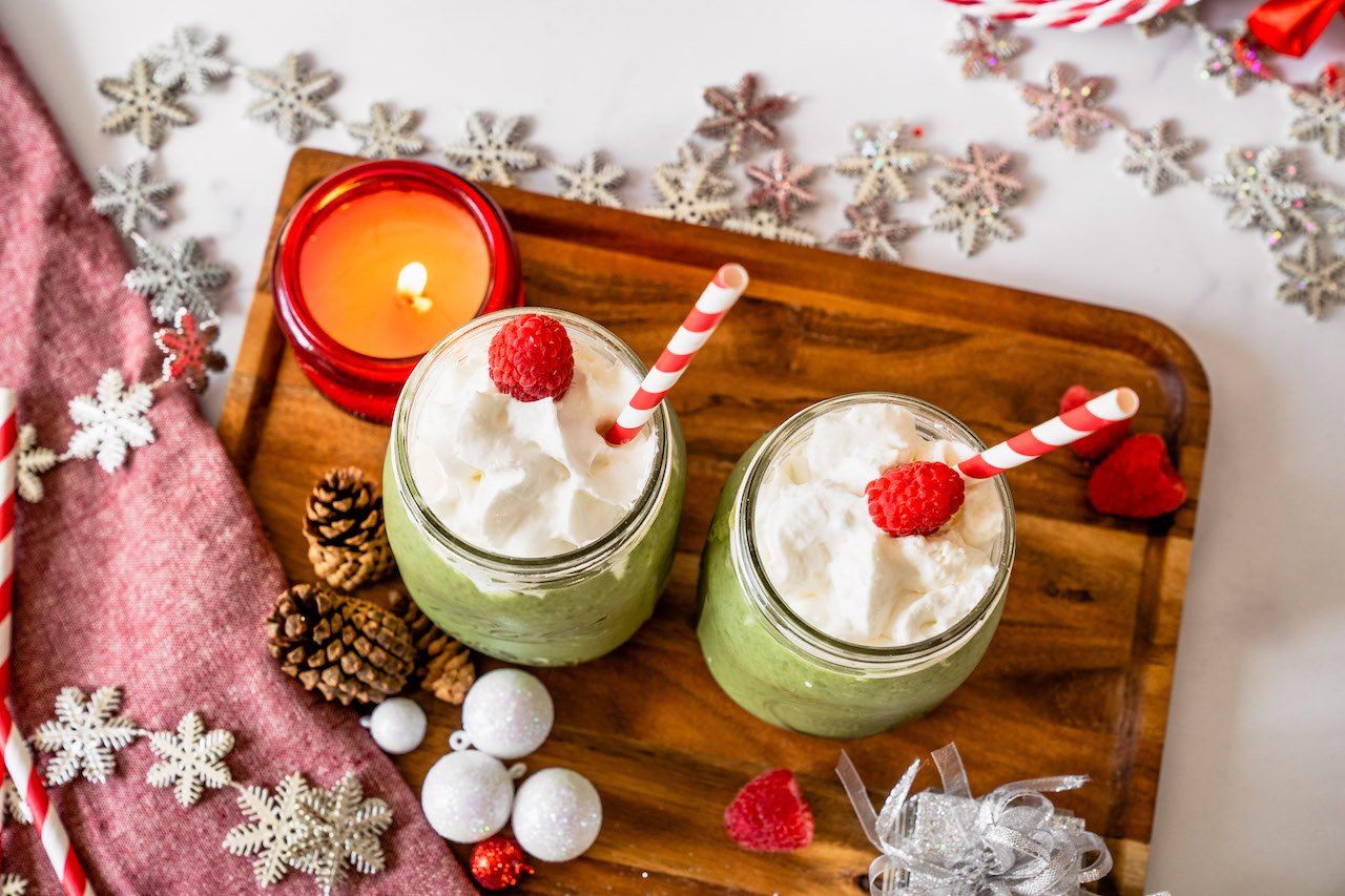 Grinch Smoothies with whip cream and raspberry toppings for extra holiday colors, as well as SkinnyFit Skinny Greens for slimming superfoods.