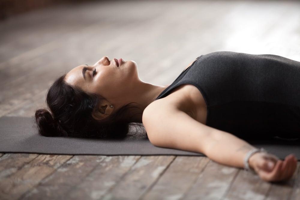 Yoga breathing woman laying on the floor meditating